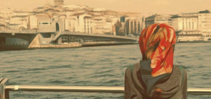 Frau steht am Ufer und schaut auf eine Brücke