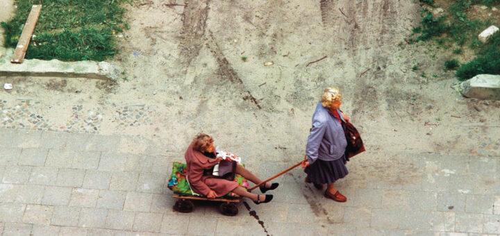 Ältere Frau zieht eine andere ältere Frau im Handwagen hinter sich her