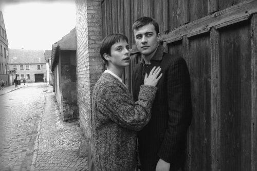 Das Filmpaar auf der Dorfstaße stehend vor einer Scheune
