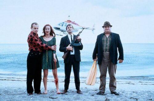 Die Hauptdarsteller am Strand stehend mit landendem Helikopter im Hintergrund.