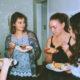 Vier Junge Frauen unterschalten sich stehnd beim Essem